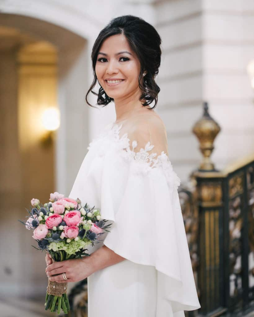 a bride holding a bouquet posing on the Grand Staircase
