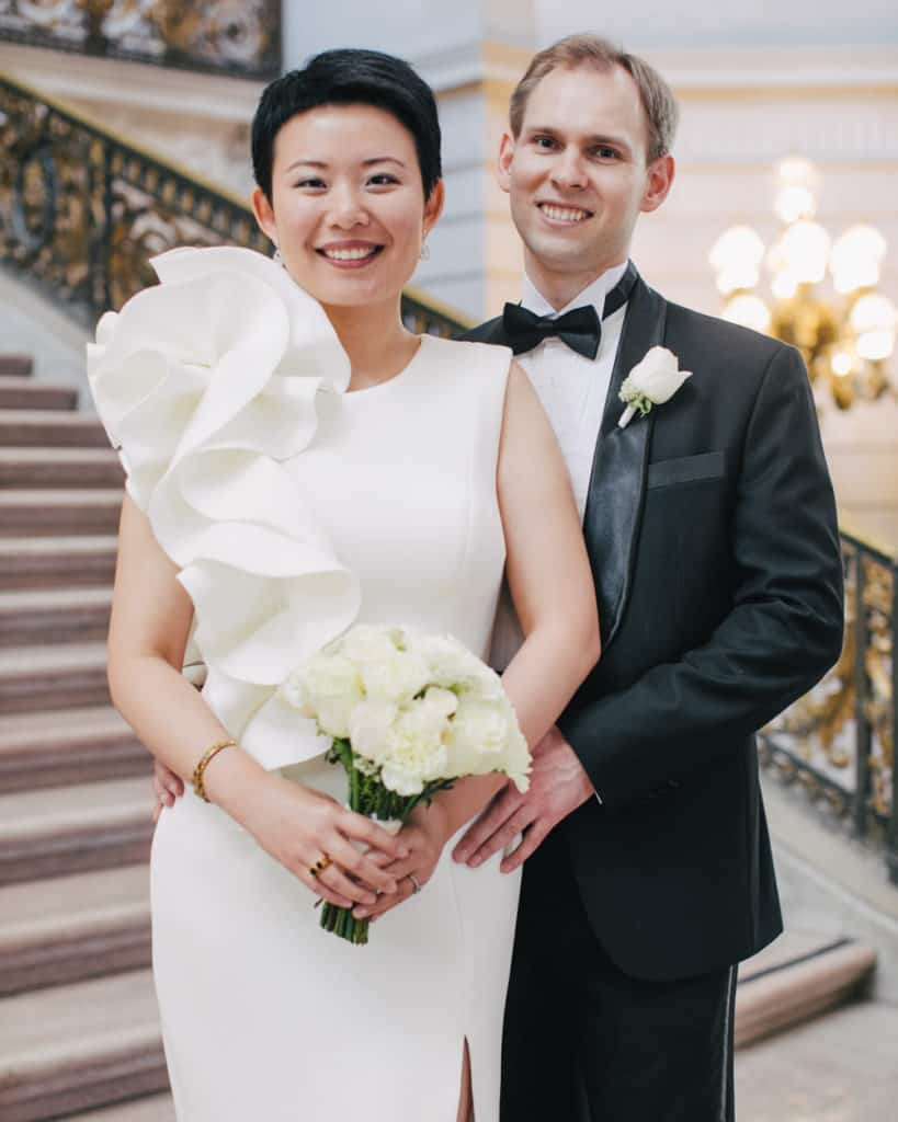 a bride in a unique retro gown holding a bouquet posing on the Grand Staircase