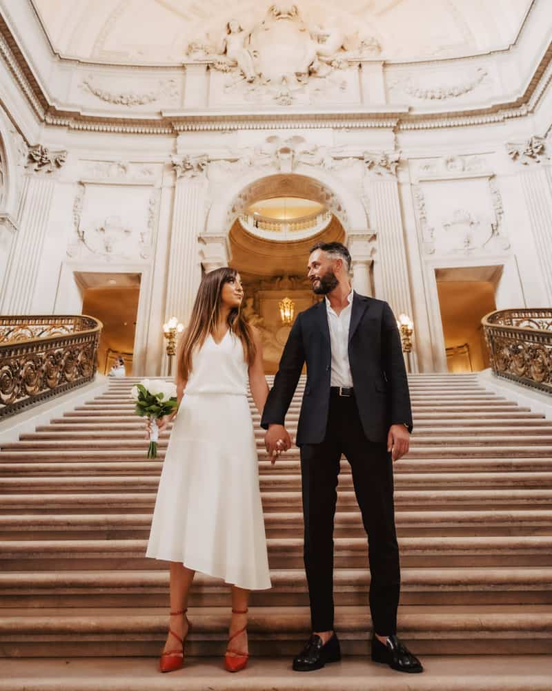 a couple posing on the grand staircase at city hall - bride has a uniquely cut dress and red shoes