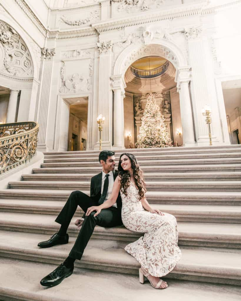 a couple sitting on the grand staircase by the Christmas tree