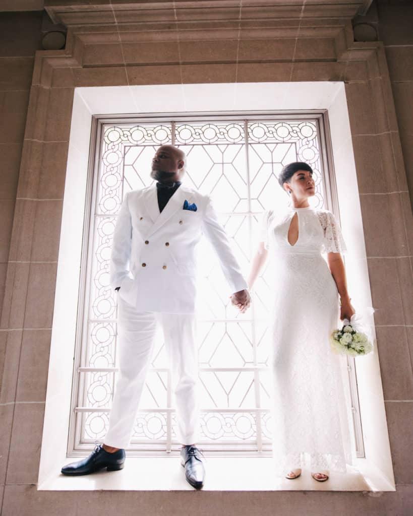 an interracial couple posing at sf city hall
