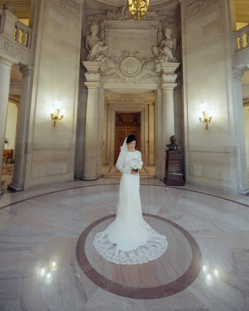 a bride with a long train dress posing in the rotunda