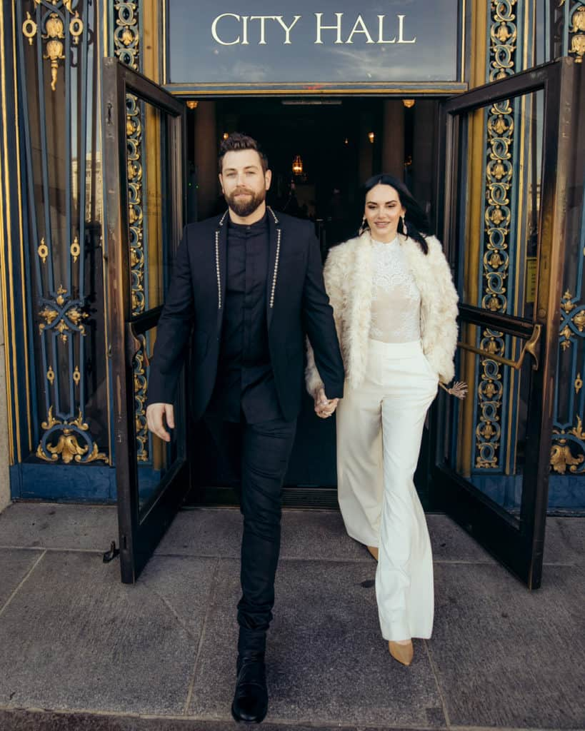 a stylish couple leaving sf city hall from the main entry