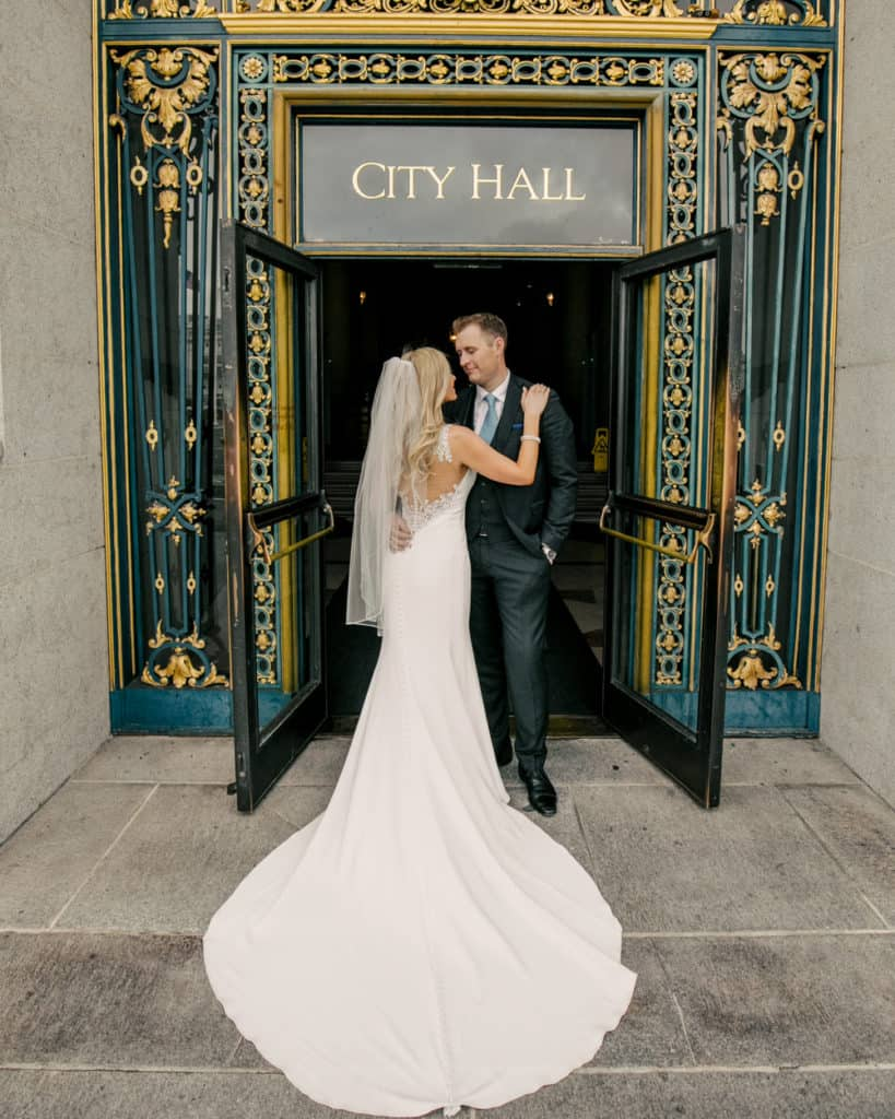 a bride with a long train posing in front of the main sf city hall entry