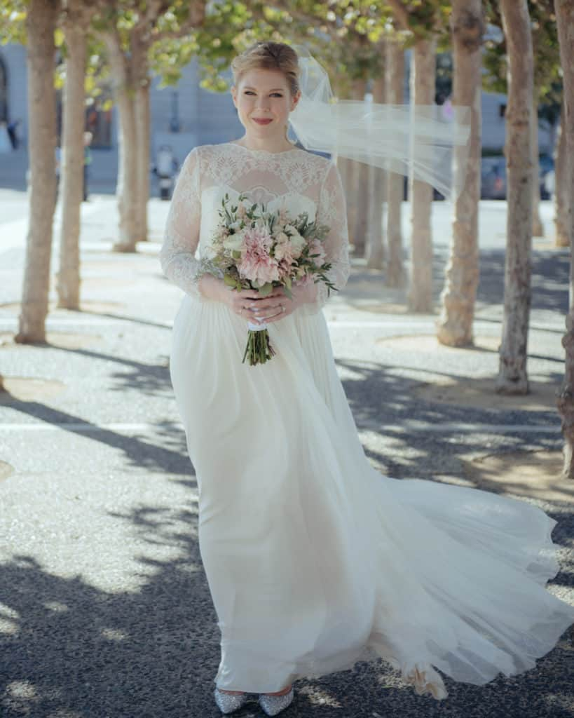 a bride posing outside of sf city hall across the street in the park