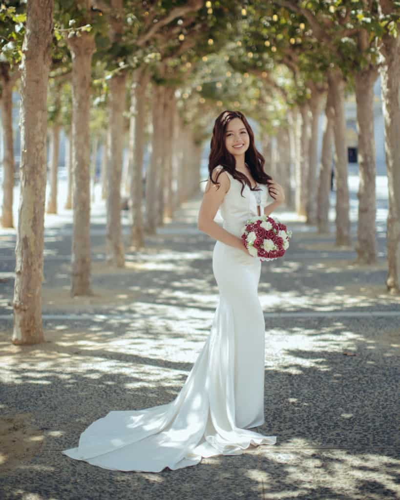 a bride posing in the tree tunnel across from city hall