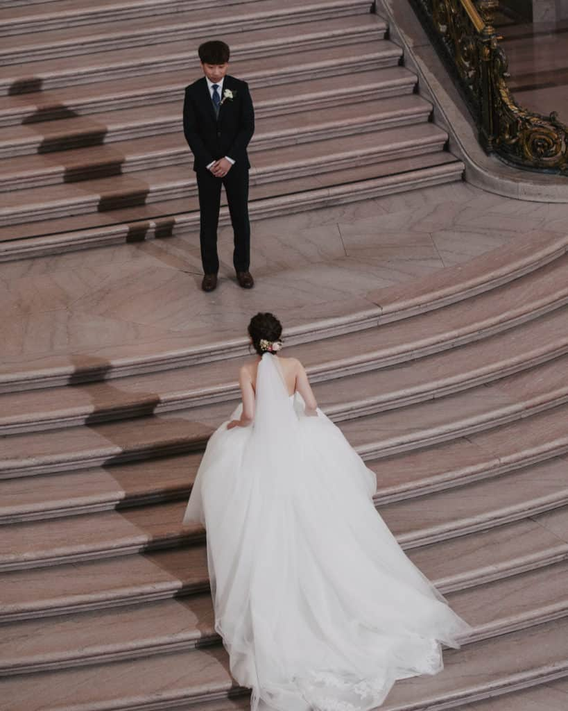 a bride walking up the grand staircase to meet the groom