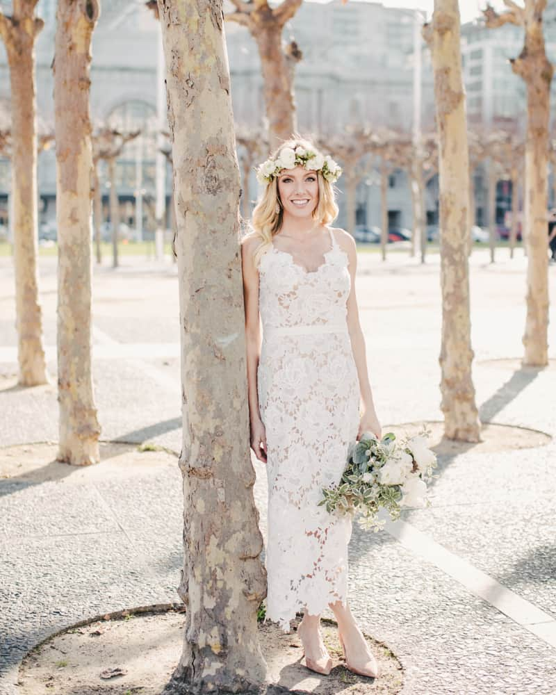 a bride in the short wedding gown posing outside of sf city hall in the park
