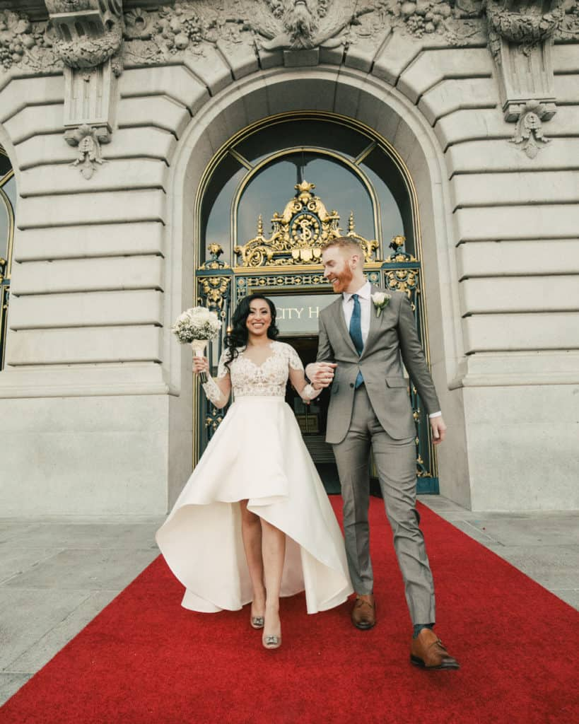 a couple walking on the red carpet at city hall