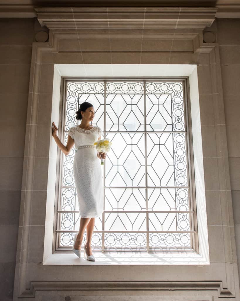 a bride standing on the 3rd froor window - white wedding gown