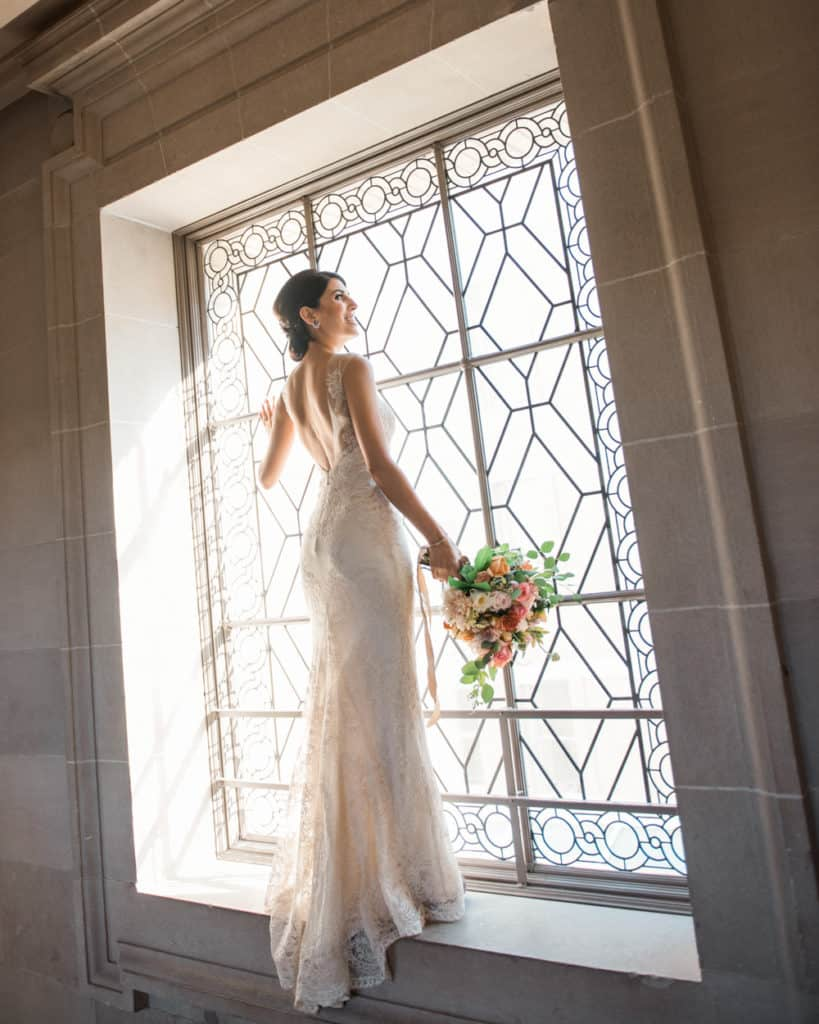 a bride posing on the 3rd froor by the window
