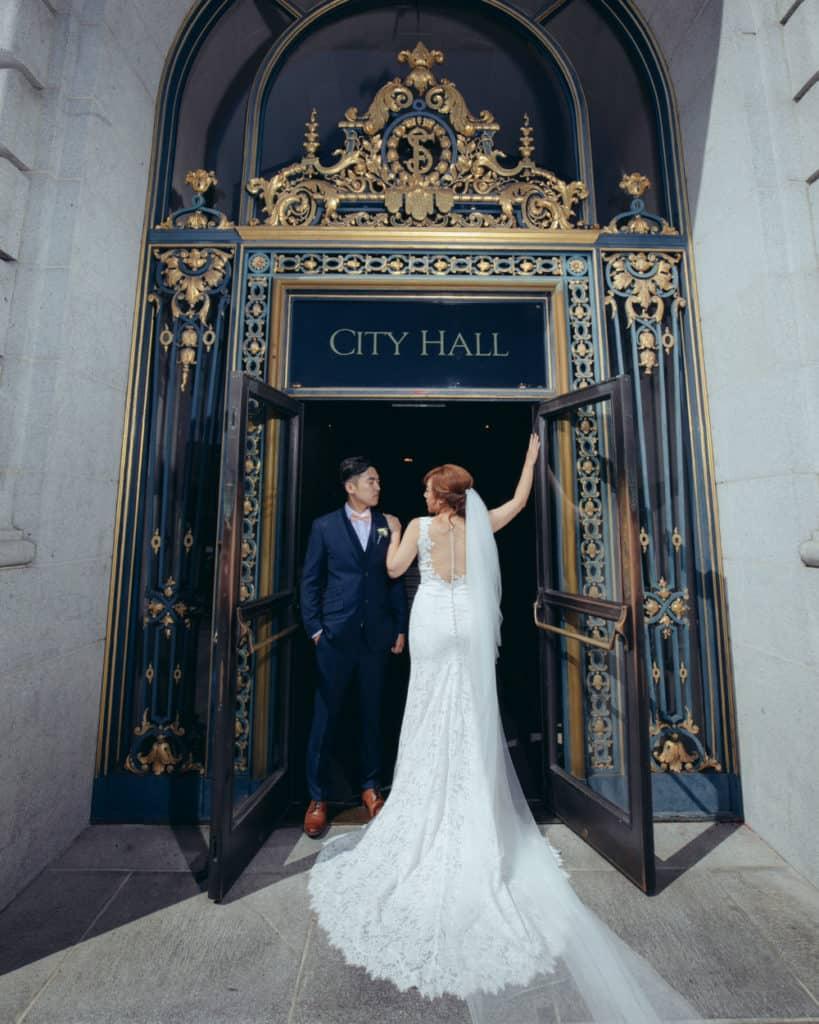 a bride with a long train posing at the main door at city hall